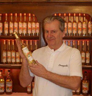 Bild: Klaus Pöchhacker vor Regal mit Orangello-Flaschen